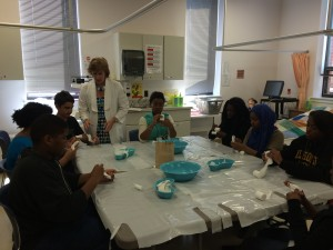 School of Nursing's Carol Ritchie helping the student make casts of their own fingers