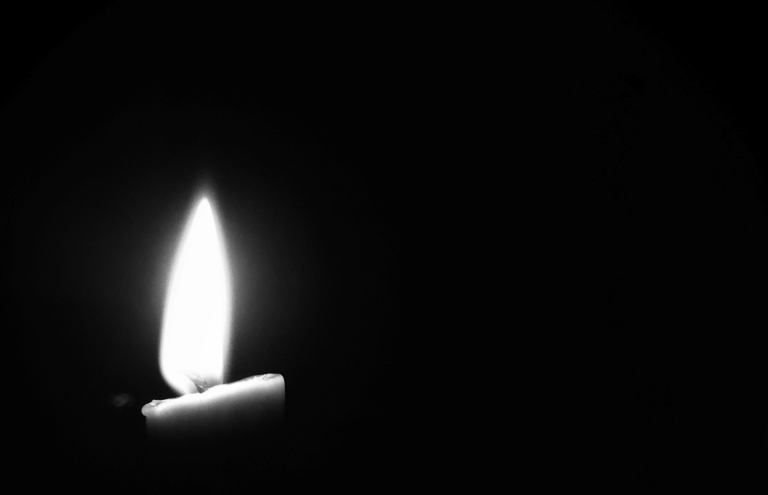 Candlelight appears amidst a black background.