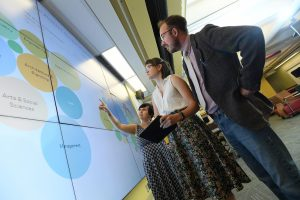 MI students Dan Phillips, Lydia Hunsberger and Crystal Vaughan at the Killam Library's data visulization wall. (Danny Abriel photo)
